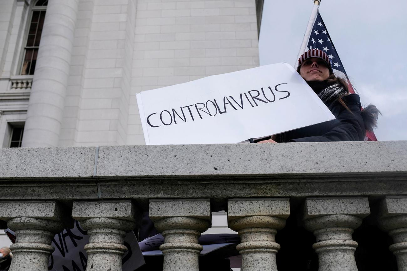 "The protestor can be seen against the backdrop of the capitol building and an American flag holding a handmade sign that reads simply, ""Controlavirus."""
