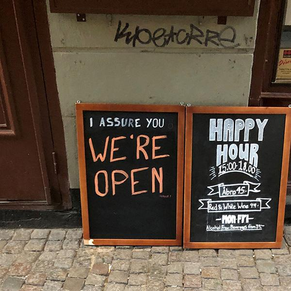 """In a country that didn't lockdown during the coronavirus pandemic, a sign assures people that the bar is open during the COVID-19 outbreak—outside a pub in Stockholm, Sweden, on March 26, 2020. Picture Shows two side-by-side chalk placards in front of a restaurant advertising a happy hour inside. One of the signs reads, """"I assure you WE'RE OPEN."""" REUTERS/Colm Fulton"""
