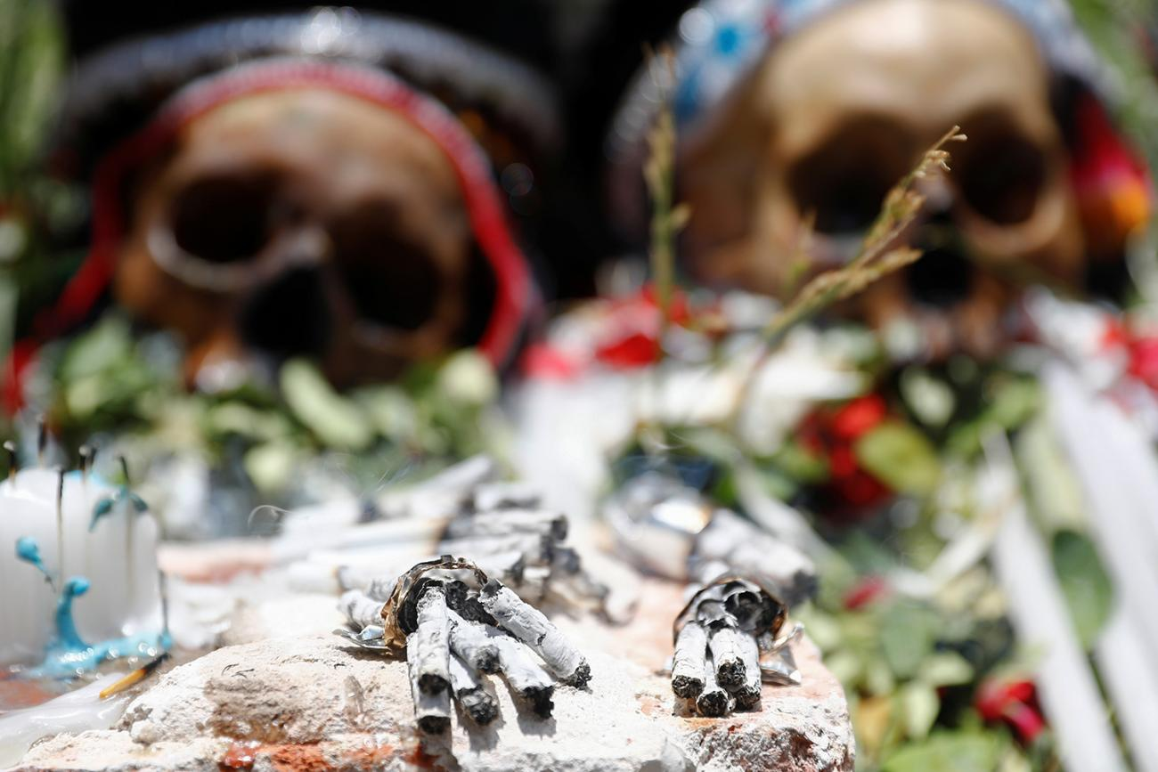 Cigarette butts are seen in front of exhibited skulls during the Day of Skulls celebrations in La Paz, Bolivia November 8, 2019. The photo shows two human skulls laid out with flowers in a ceremonial way with a number of burned cigarettes in the foreground. REUTERS/Kai Pfaffenbach