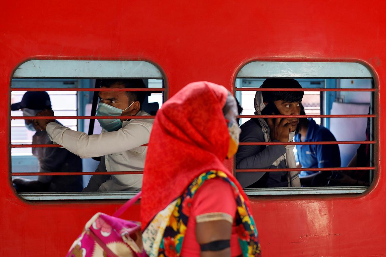 Migrant workers, who were stranded in the western state of Gujarat due to a government lockdown, inside a train as they leave for their homes in Ahmedabad, India, on May 2, 2020. The image shows a bright red train with people inside and a woman walking by the train outside. REUTERS/Amit Dave