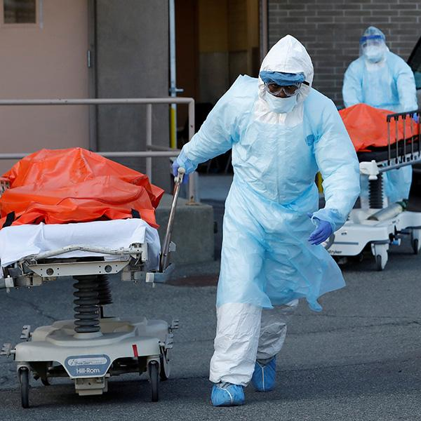 Health care workers wheel the bodies of deceased people from the Wyckoff Heights Medical Center during the coronavirus outbreak in the Brooklyn borough of New York City on April 4, 2020. The photo shows two people in blue protective suits wheeling people away from a hospital entrance. REUTERS/Andrew Kelly