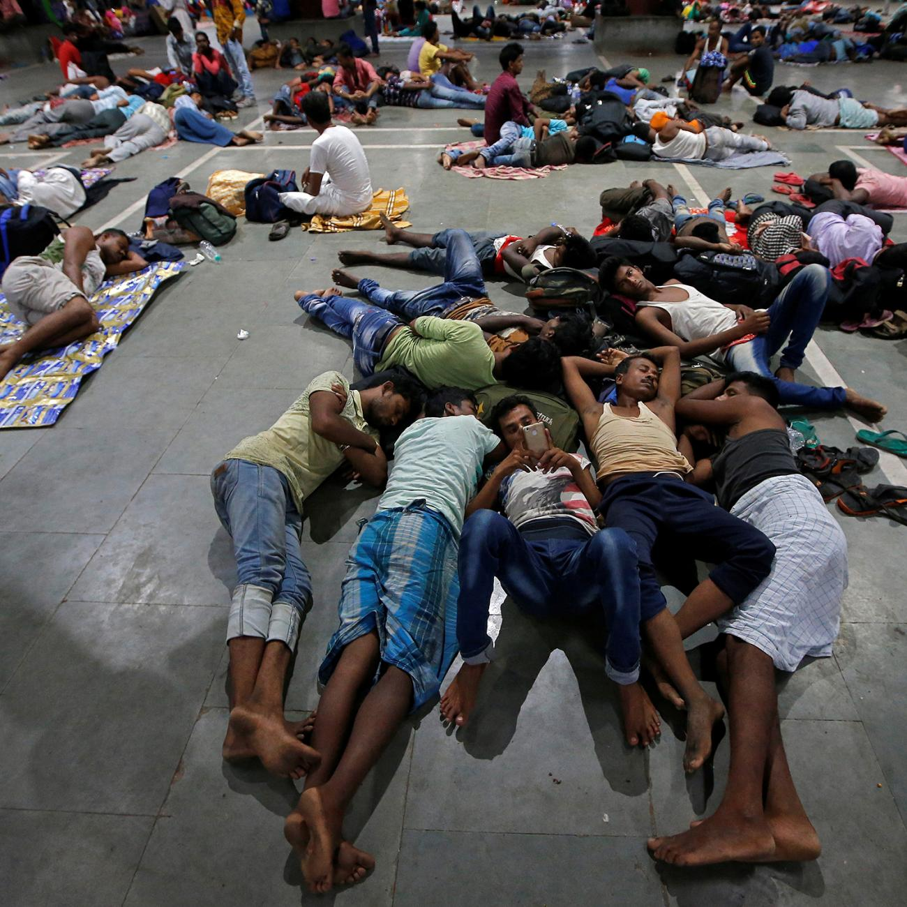 The photo shows a large number of people stretched out on concrete resting.