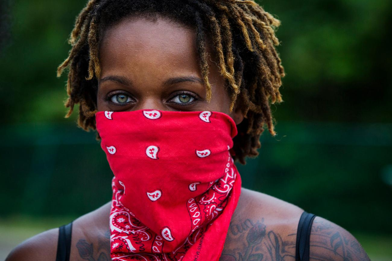 A woman looks into the camera during a demonstration to protest the shooting of Michael Brown and the resulting police response to protests in Ferguson, Missouri August 15, 2014. The photo shows a woman with a red bandana tied around her face. REUTERS/Lucas Jackson