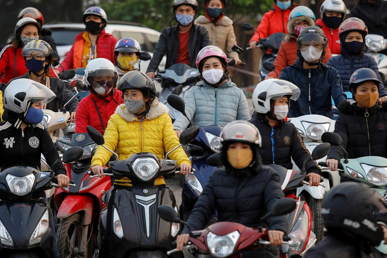 The photo shows a number of people on motorcycles wearing masks.