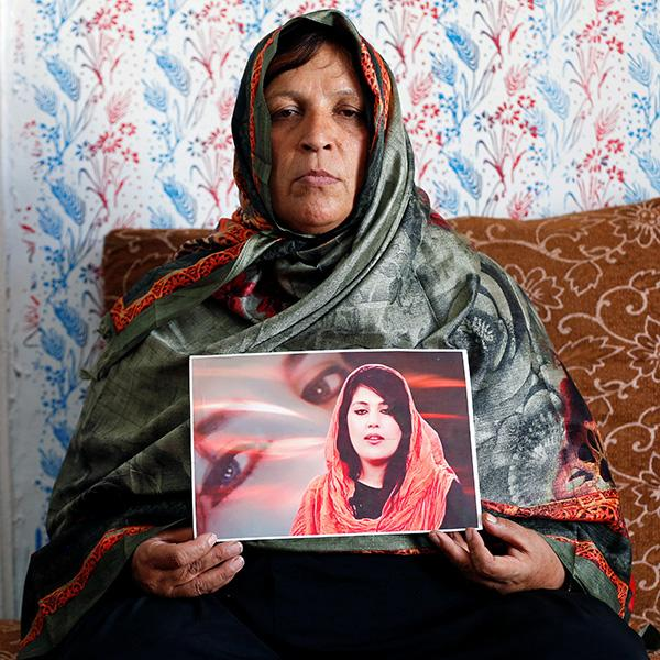 Anisa Mangal on May 14, 2019 holds a photo of her daughter Mena Mangal, an Afghan journalist, parliamentary adviser, and advocate of women's rights who was killed last year in Kabul, Afghanistan. Picture shows the mother stermly looking at the camera holding a photo of her daughter. REUTERS/Mohammad Ismail