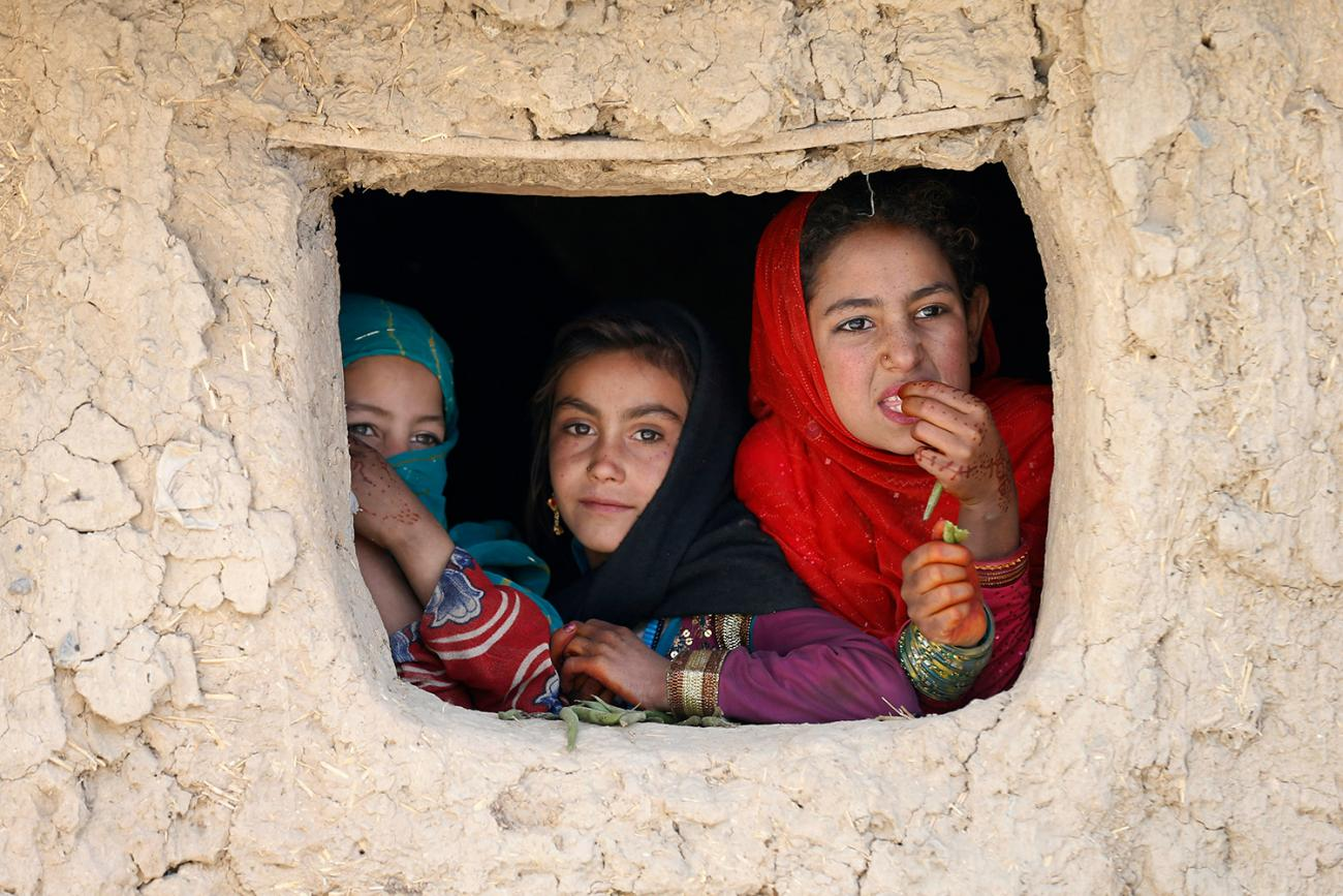 The photo shows three girls looking out the window of a building.