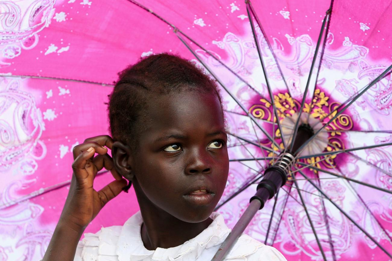 Picture shows a girl looking to her left standing under a pink umbrella.