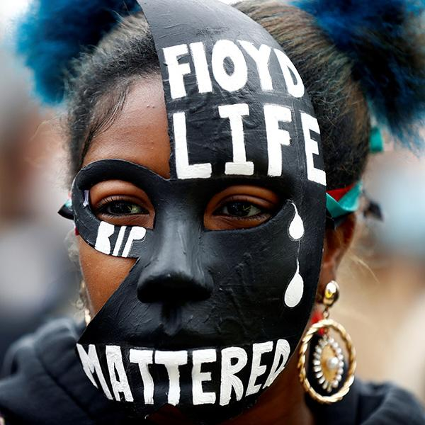 """A woman wears a mask during a Black Lives Matter protest in Centenary Square in Birmingham, England following the death of George Floyd who died in police custody in Minneapolis, on June 4, 2020. The picture shows a woman in a striking mask adorned with the words Floyd Life """"Mattered."""" REUTERS/Jason Cairnduff"""