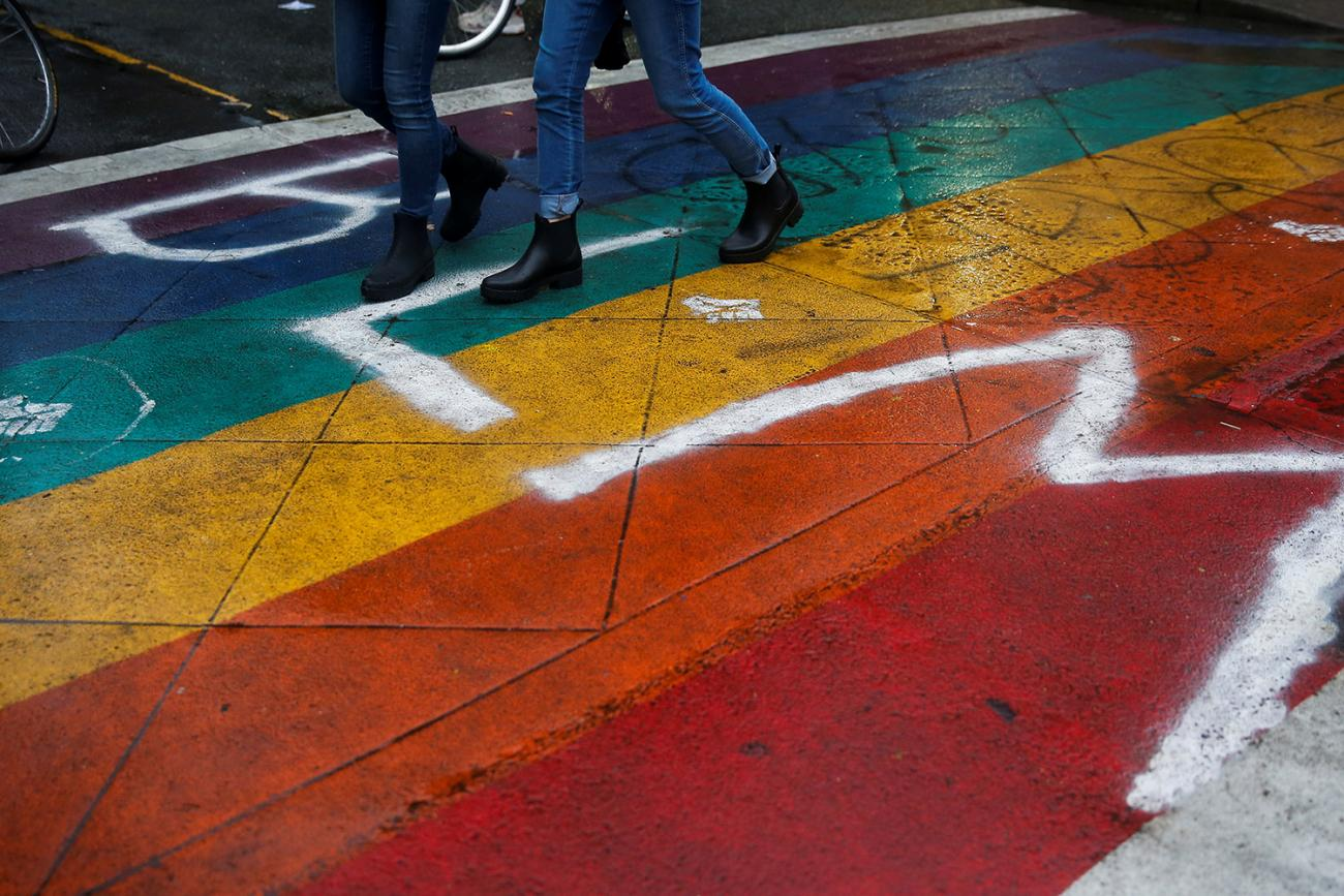 "Picture shows boots marching over a rainbow-painted section of street adorned with spray paint reading ""BLM."""