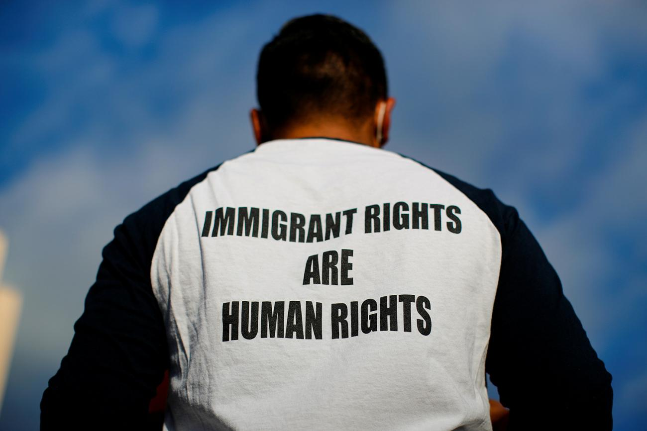"The photo shows a man with his back to the camera wearing a black-and-white baseball shirt emblazoned with the message, ""Immigrant rights are human rights."""
