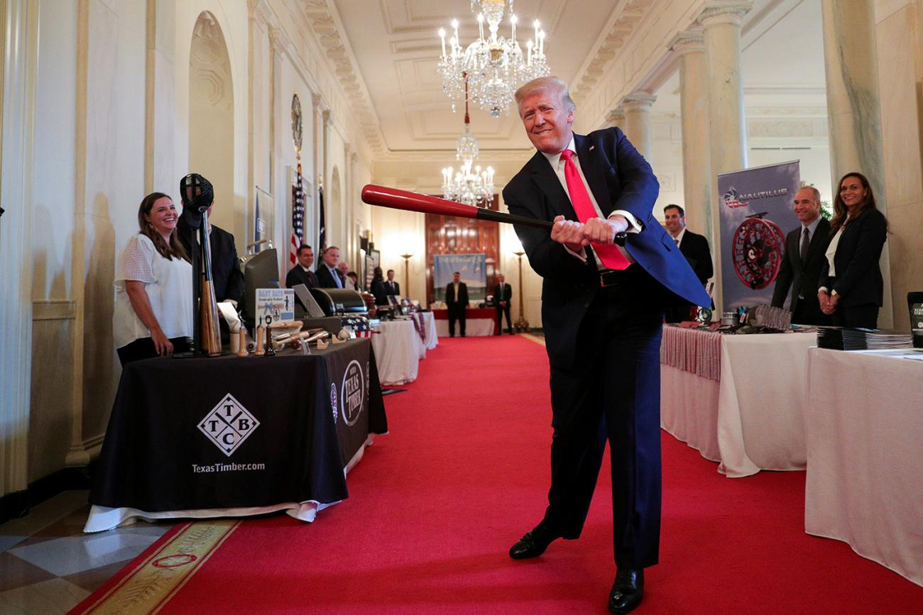 """U.S. President Donald J. Trump swings a wooden baseball bat, celebrating a new jobs report, as he attends a """"Spirit of America Showcase"""" event at the White House in Washington, DC, on July 2, 2020. The photo shows the president hamming it up with people staffing booths and swinging a red bat. REUTERS/Tom Brenner"""