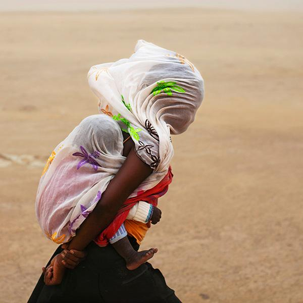 Going out in a storm is a tough choice. Here a woman braves a sandstorm in Timbuktu, Mali, on July 29, 2013. Far worse is the decision many face today whether to brave COVID-19 for other health care.  The photo shows a woman with a baby on her back walking through a desert. The wind is blowing strongly, as evidenced by the billowing cloth on their heads. REUTERS/Joe Penney