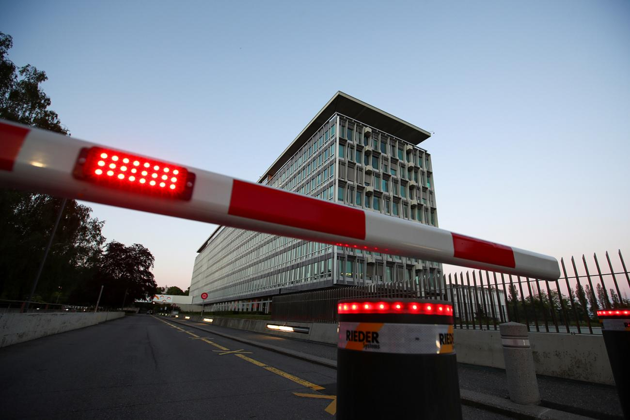 The photo shows the WHO building at night with a red and white guard barrier lowered to block the street entrance.