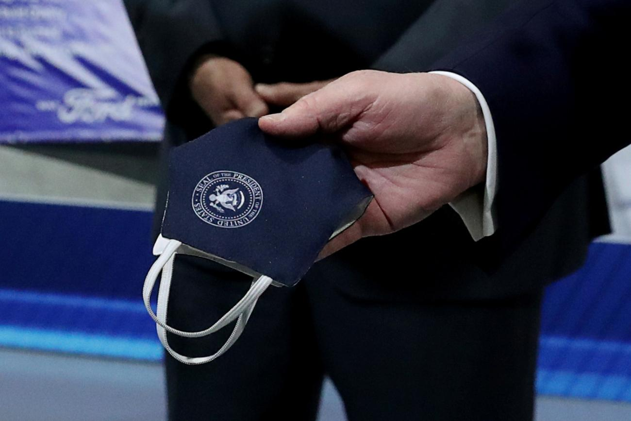 Photo shows a pair of hands holding the mask, which is printed with the seal of the White House.