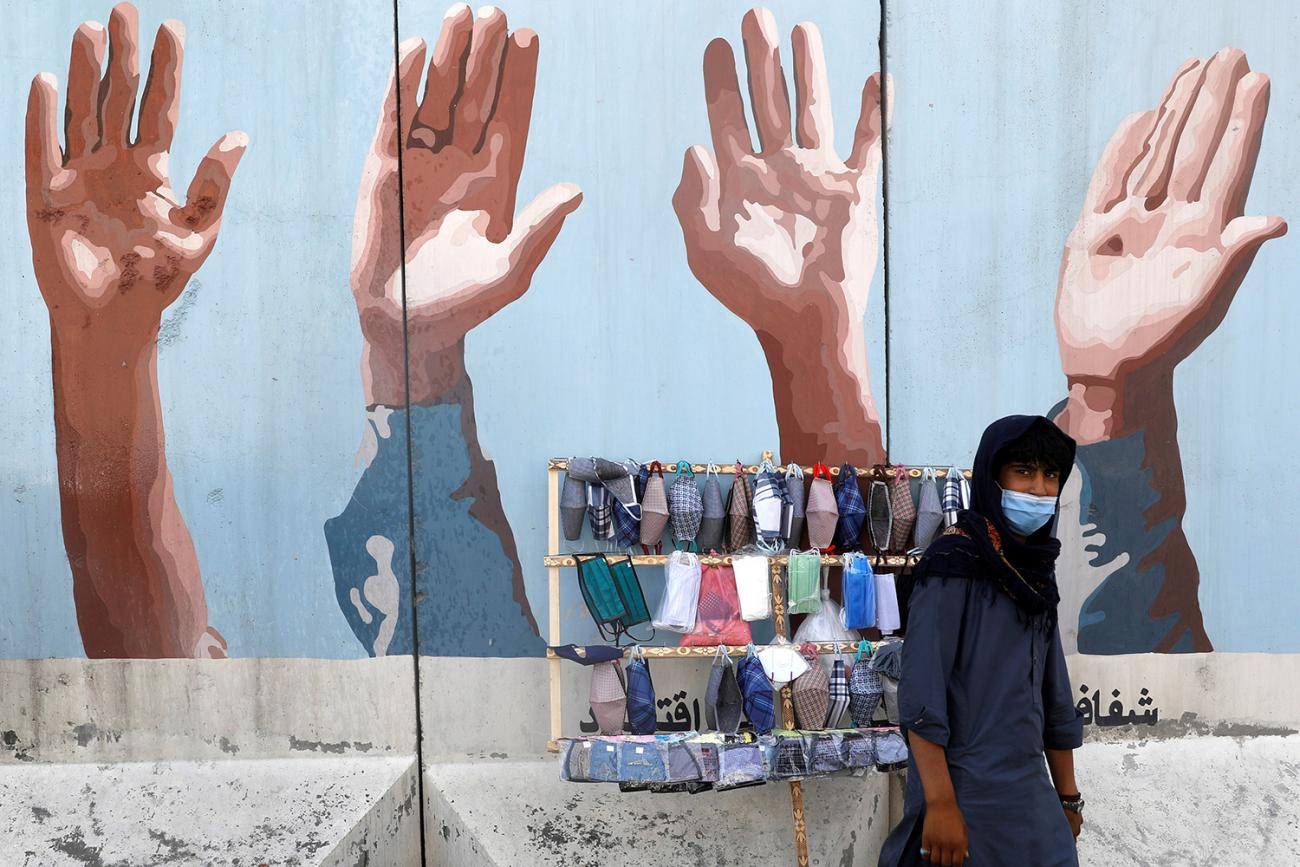 An Afghan man sells protective face masks during the coronavirus disease (COVID-19) outbreak in Kabul, Afghanistan June 18, 2020. The photo shows a man in front of a small cart with masks on display. in the background is a mural of hands raised. REUTERS/Mohammad Ismail