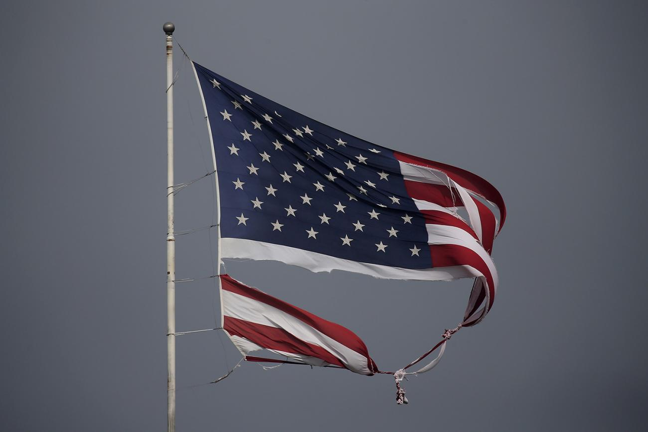 A tattered U.S. flag damaged in Hurricane Harvey, flies in Conroe, Texas, on August 29, 2017. The photo shows a torn U.S. flag blowing against a dark grey sky. REUTERS/Carlo Allegri