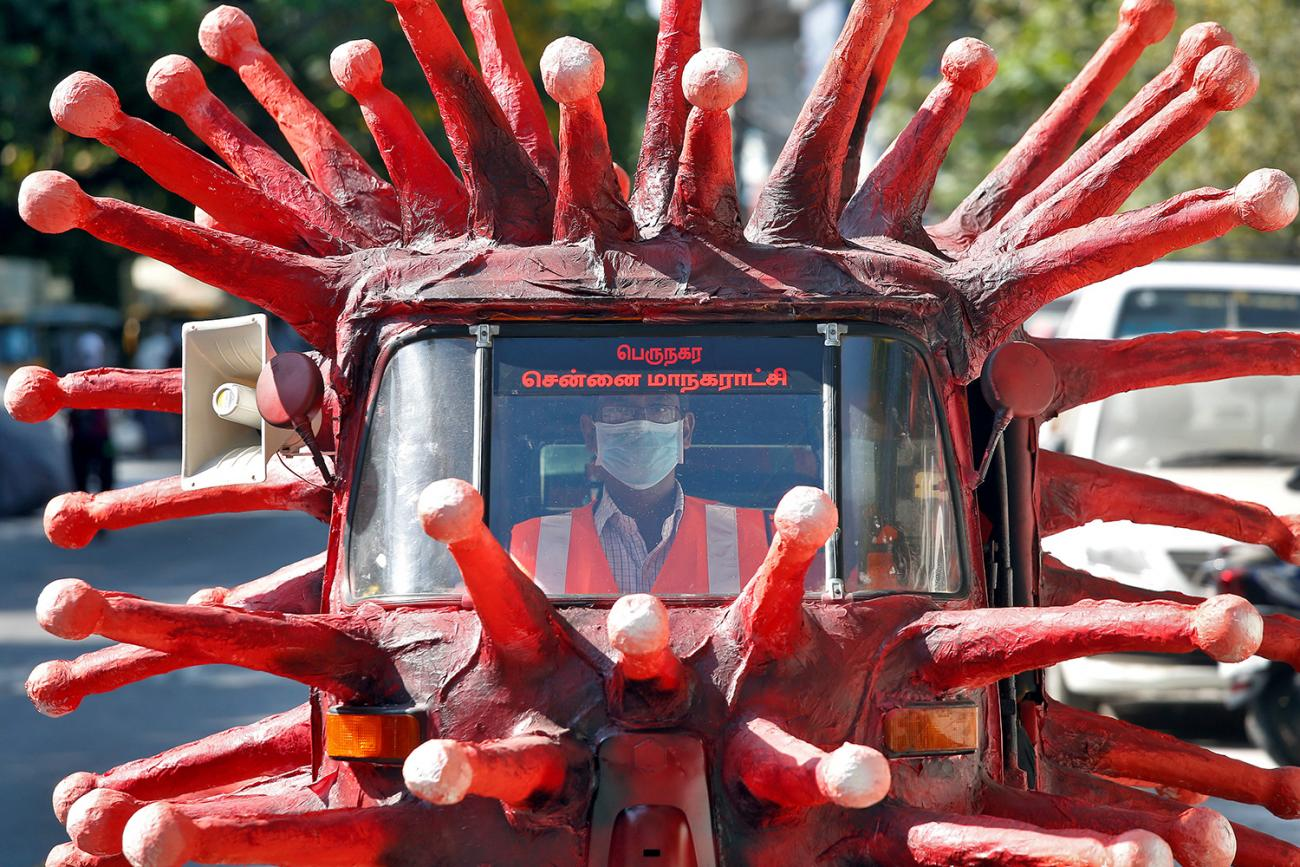 A man drives an auto-rickshaw depicting the coronavirus to create awareness about staying at home during a nationwide lockdown to prevent the spread of COVID-19—in Chennai, India, on April 23, 2020. The image shows a vehicle painted red and covered with crown spikes reminiscent of the virus, which appear to be made of paper mache. REUTERS/P. Ravikumar