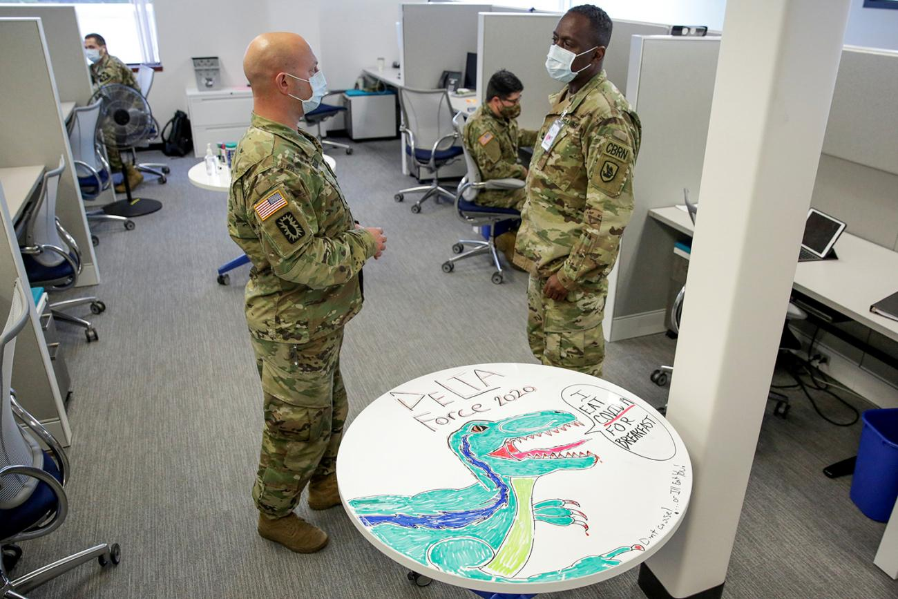"A militarized approach to contact tracing is shown here as National Guard members at the Washington State Department of Health support contact tracing efforts in Tumwater, Washington—on May 20, 2020. The photo shows the guard members standing around a cubicle space talking. A table in the foreground is decorated with a drawing of a dinosaur and emblazoned with the words ""I eat COVID-19 for breakfast. REUTERS/Jason Redmond"