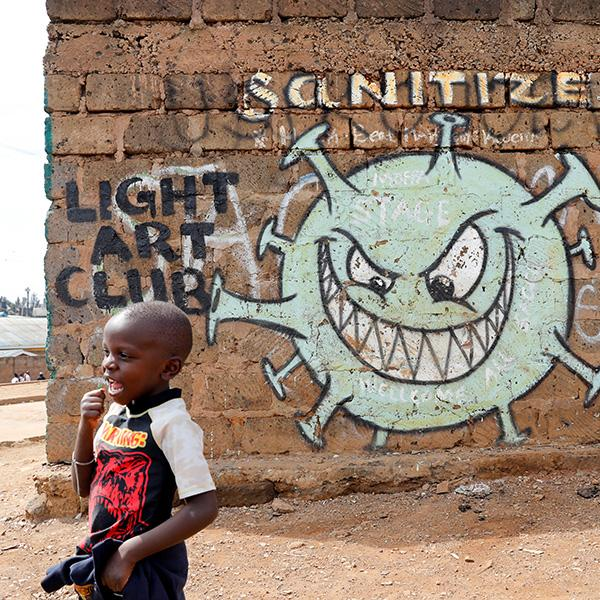 A boy stand in front of a graffiti promoting the fight against the coronavirus disease (COVID-19) in the Mathare slums of Nairobi, Kenya, on May 22, 2020. This is a powerful photo of a young boy walking in front of a sinister depiction of the virus with a face that appears to be sneeringly looking at the boy. REUTERS/Baz Ratner