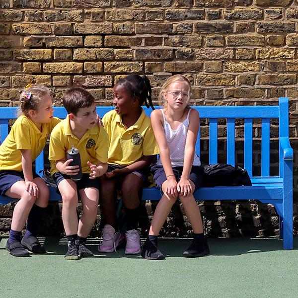 Four of the world's two billion children under the age of fourteen sit on a bench in the playground at St John's Primary School in in London on July 16, 2020 amid the spread of coronavirus. The photo shows four kids on a bench. One of them is looking at the camera. REUTERS/Kevin Coombs