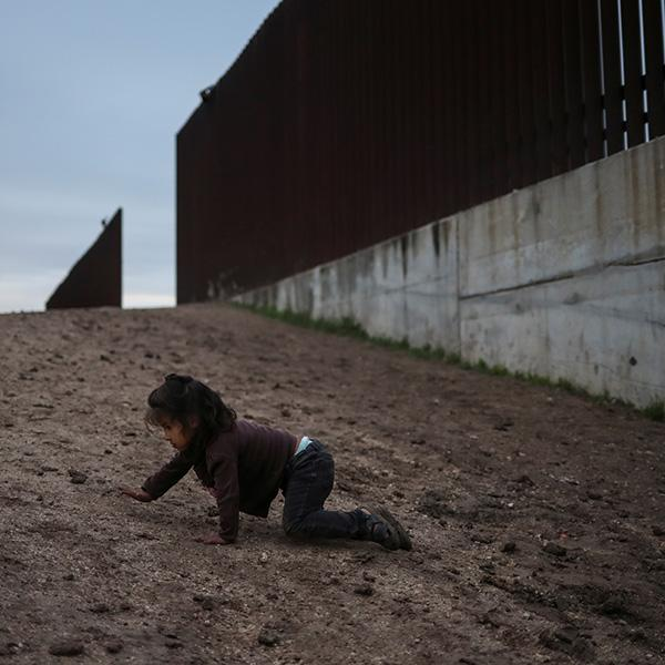 Amy, a two-year-old migrant from Honduras seeking asylum with her parents, crawls on a dirt road after crossing the Rio Grande river into the United States in Penitas, Texas, on April 1, 2019. The photo shows a small child craling on the ground near a giant border fence. REUTERS/Adrees Latif