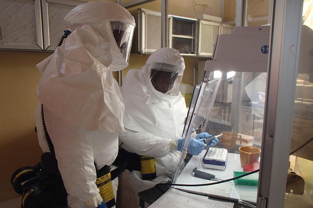 The photo shows two workers in full body protective gear working under a hood.