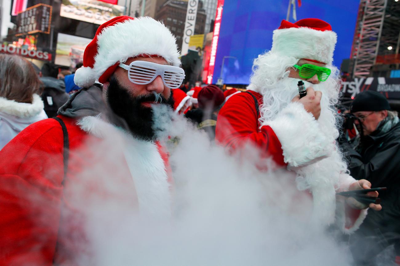 The photo shows several santas in a row smoking on vapor devices.