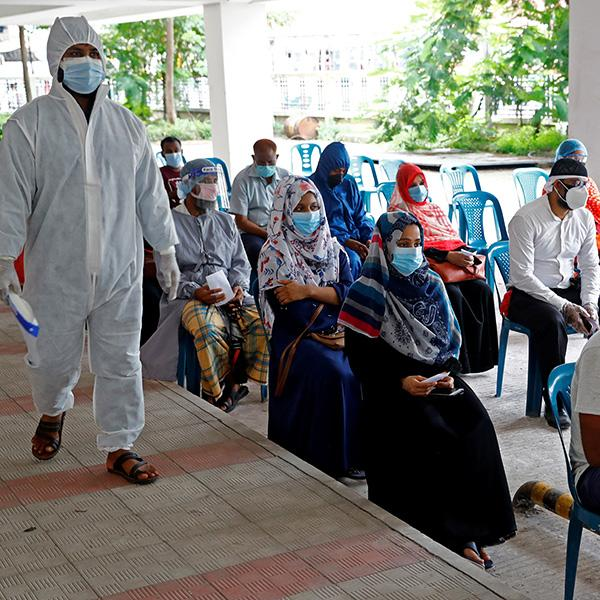 People at a coronavirus testing center on July 2, 2020 in Mugda Medical College in Dhaka, Bangladesh, where half of the medical equipment in public health facilities goes unused according to the authors. The photo shows a crowd of people wearing masks waiting on line in chairs while a health worker in full protective gear walks beside them. REUTERS/Mohammad Ponir Hossain