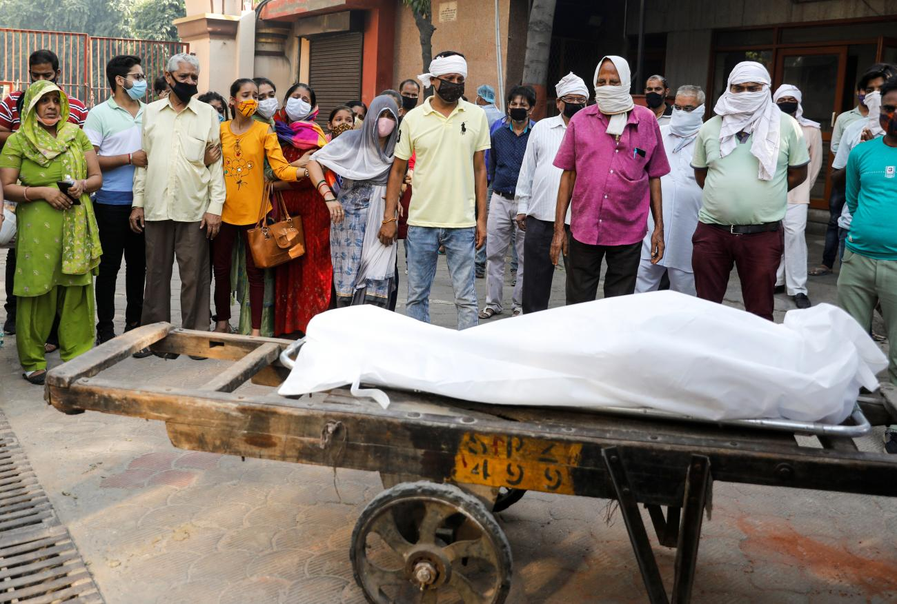 Relatives mourn as they stand next to the body of a man who died of COVID-19 before his cremation at a crematorium in New Delhi, India, September 28, 2020.