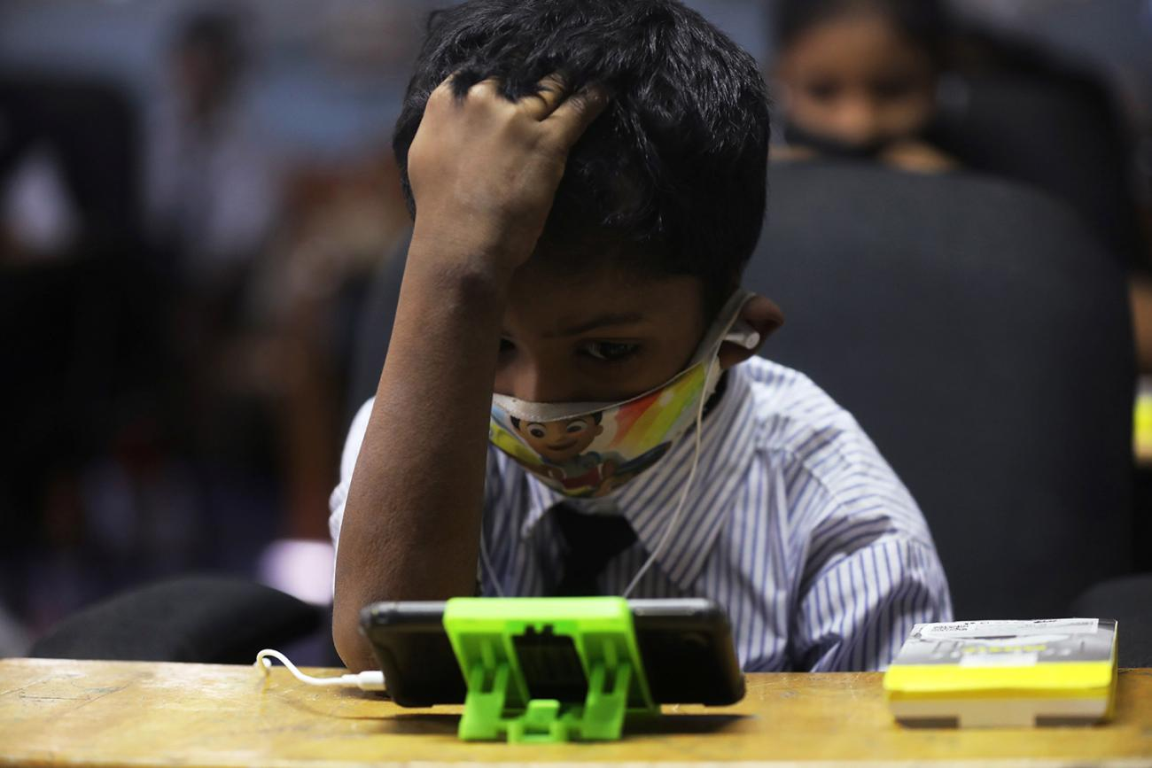 A student watches an online lecture in a digital mobile education library—which provides mobile phones to children who lack access for education during COVID-19 in Mumbai, India, on October 16, 2020. The photo shows a small child at a school desk with a mobile phone on the table in front of them. REUTERS/Francis Mascarenhas
