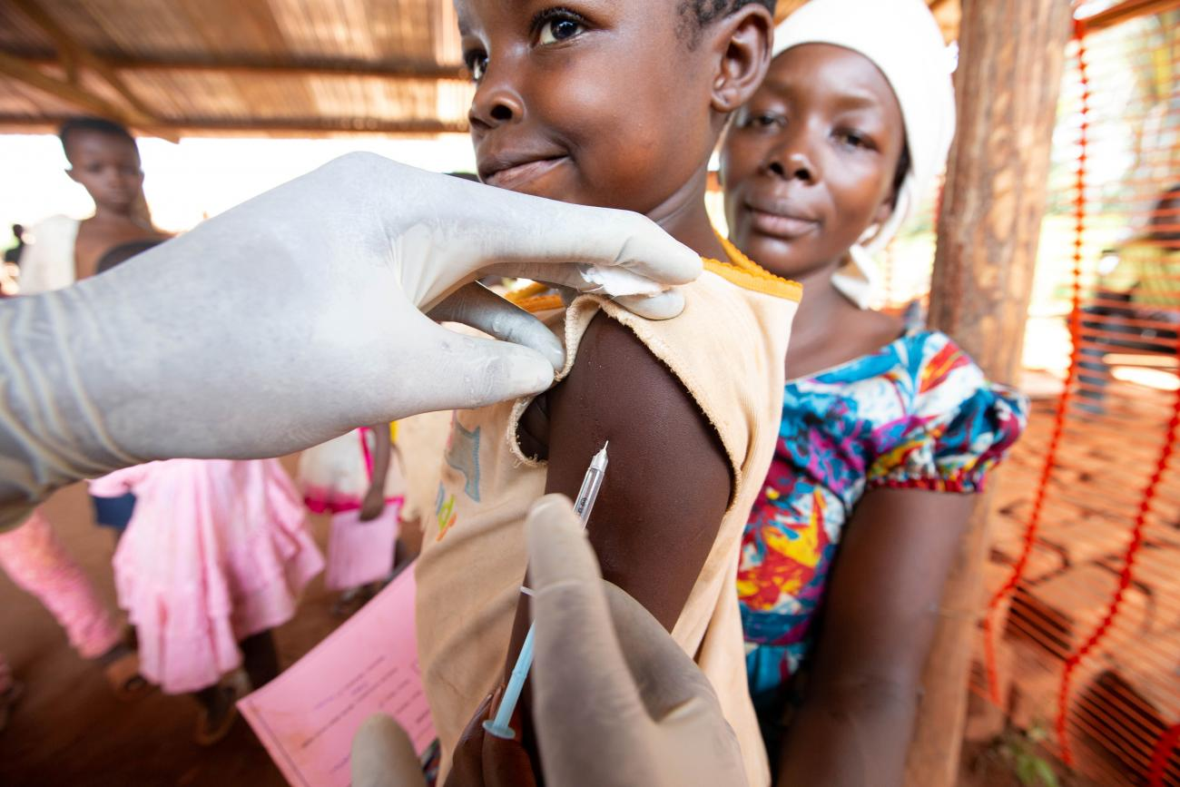 Picture shows a small child receiving a jab in the arm while an adult, presumably the child's caregiver, looks on in the background.