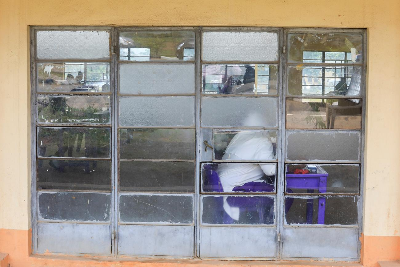 The photo shows a test taker in full protective gear inside a classroom in a picture taken from outside.