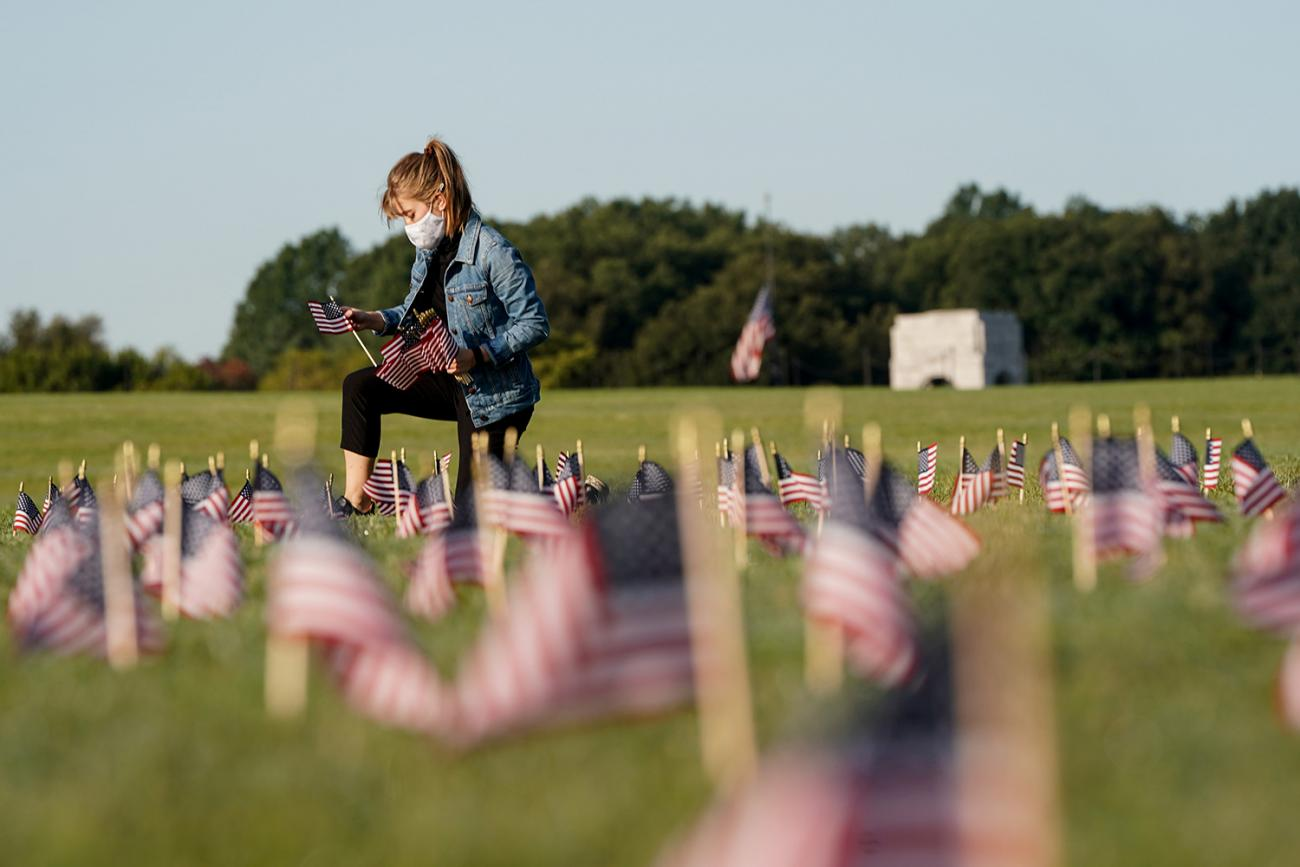 A volunteer places American flags on the National Mall in Washington DC—representing some of the more than 200,000 lives lost in the United States to coronavirus—on September 22, 2020. The photo shows a young woman on one knee planting a small American flag in the ground. Many more can be seen blurred and out of focus in the foreground. REUTERS/Joshua Roberts