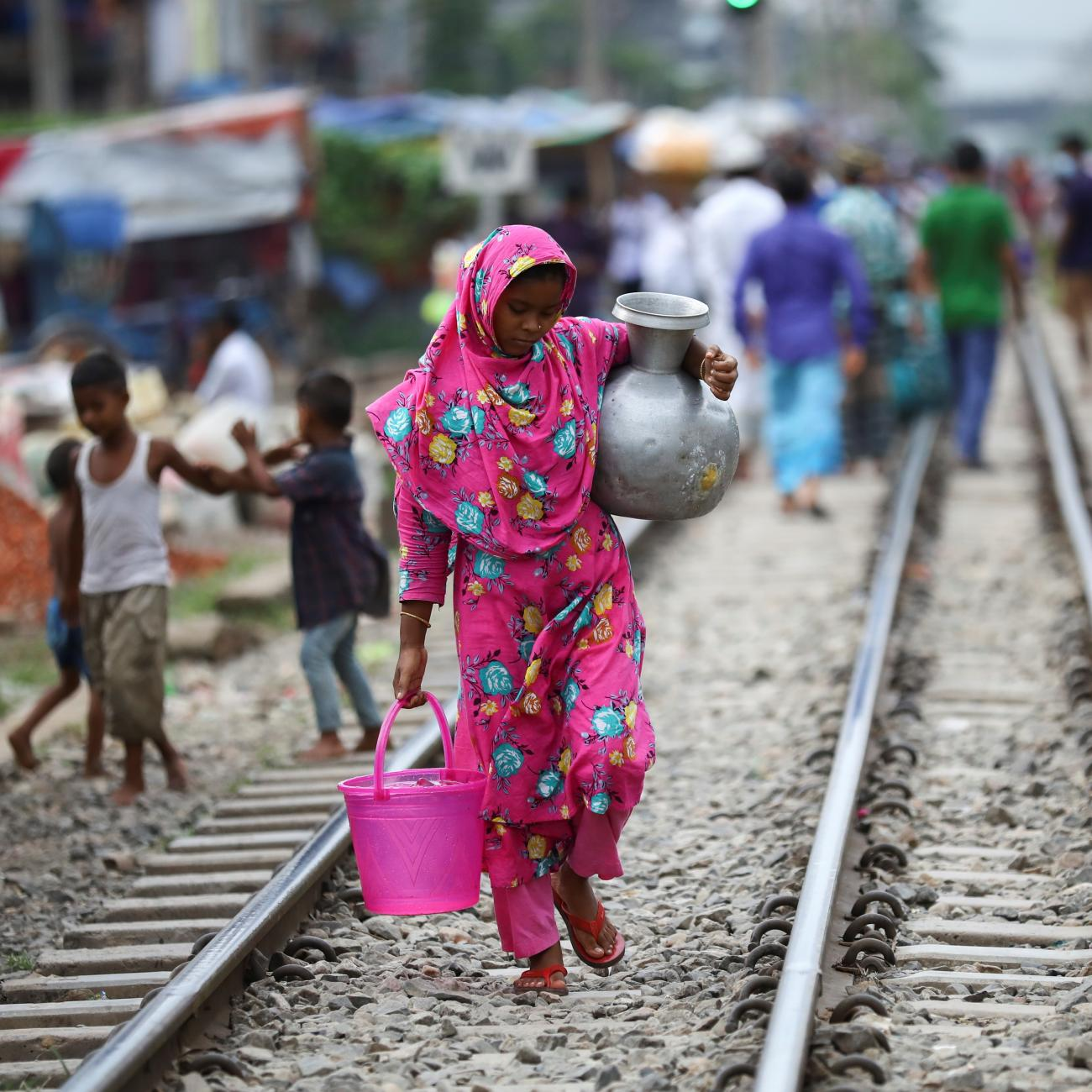 A slum dweller woman carries drinking water in Dhaka, Bangladesh, September 15, 2020. REUTERS/Mohammad Ponir Hossain