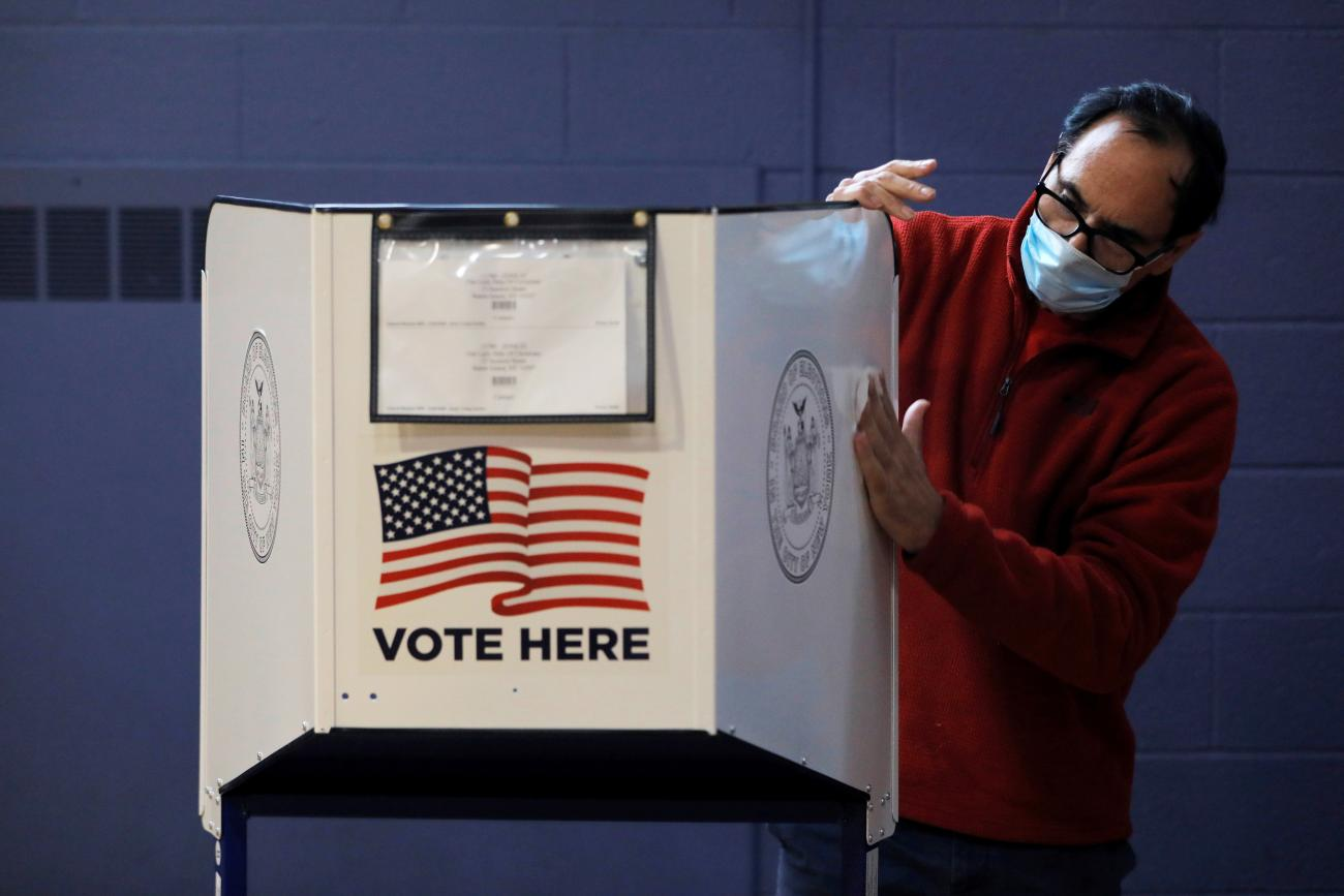 A man sanitizes a privacy booth to fight the spread of COVID-19 at a polling station in New York City, United States, on October 25, 2020. REUTERS/Andrew Kelly