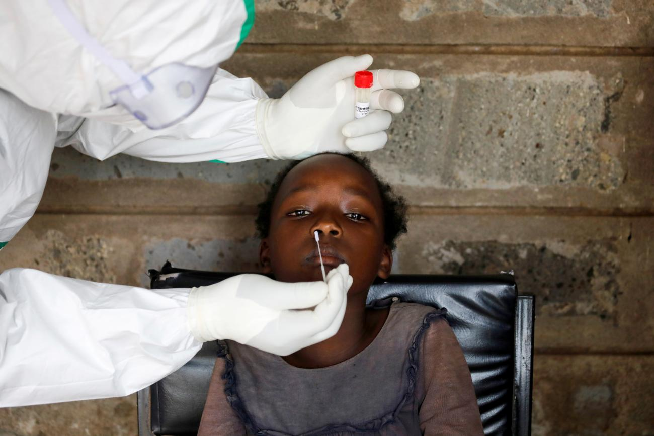 A health worker collects a swab sample from a young girl during free mass testing for the coronavirus disease (COVID-19) in Kibera slums of Nairobi, Kenya
