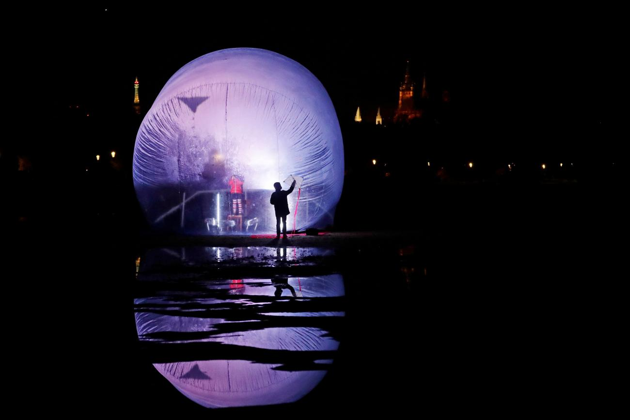 """A child flies a kite inside a giant inflatable plastic bubble during a performance of the artistic group Cirk La Putyka called """"Isolation"""" in a park, as the spread of the coronavirus disease (COVID-19) continues in Prague, Czech Republic"""