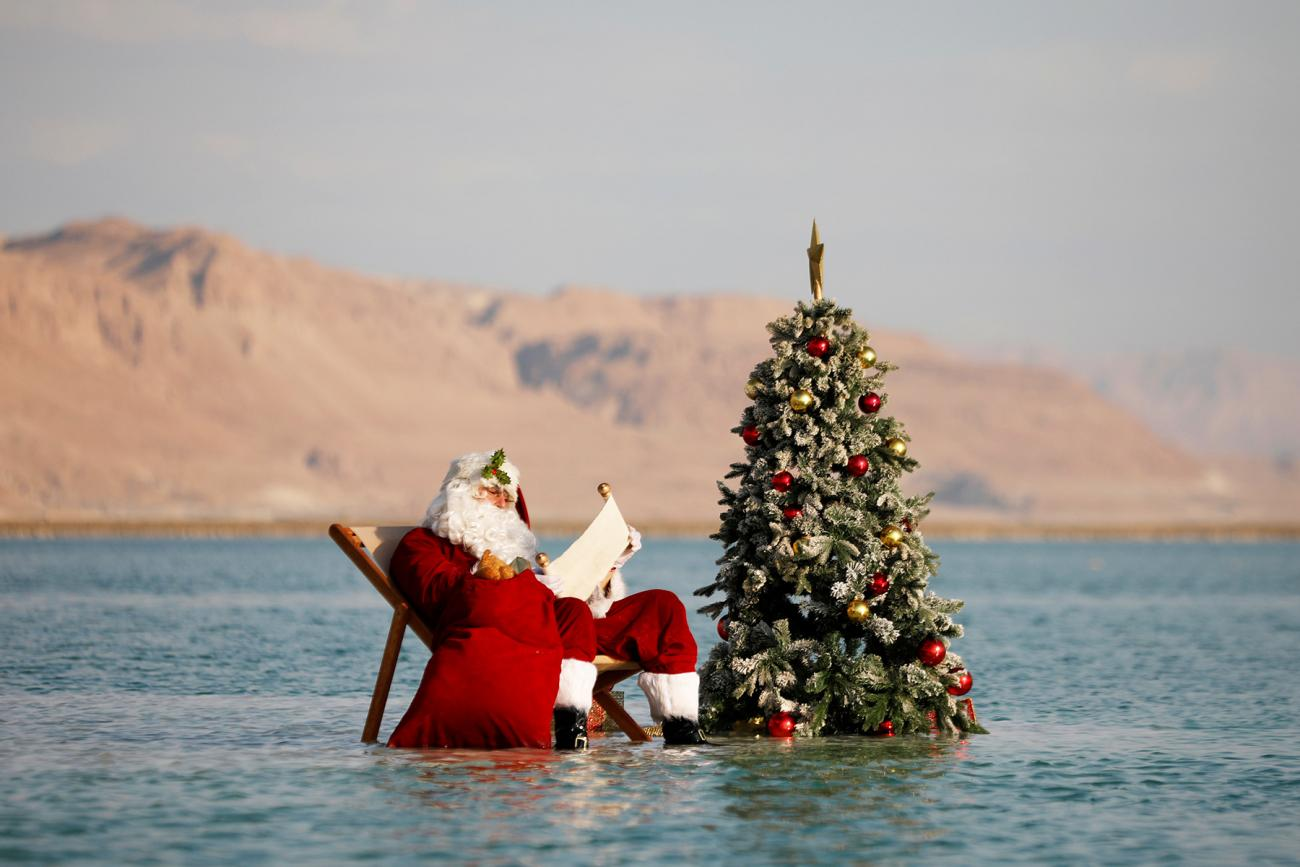 A man, wearing a red Santa Claus costume complete with a hat, beard, and bag full of toys, holds a scroll as he poses for a picture while sitting next to a decorated Christmas tree on a salt formation in the Dead Sea, near Ein Bokeq, Israel on November 15, 2020.
