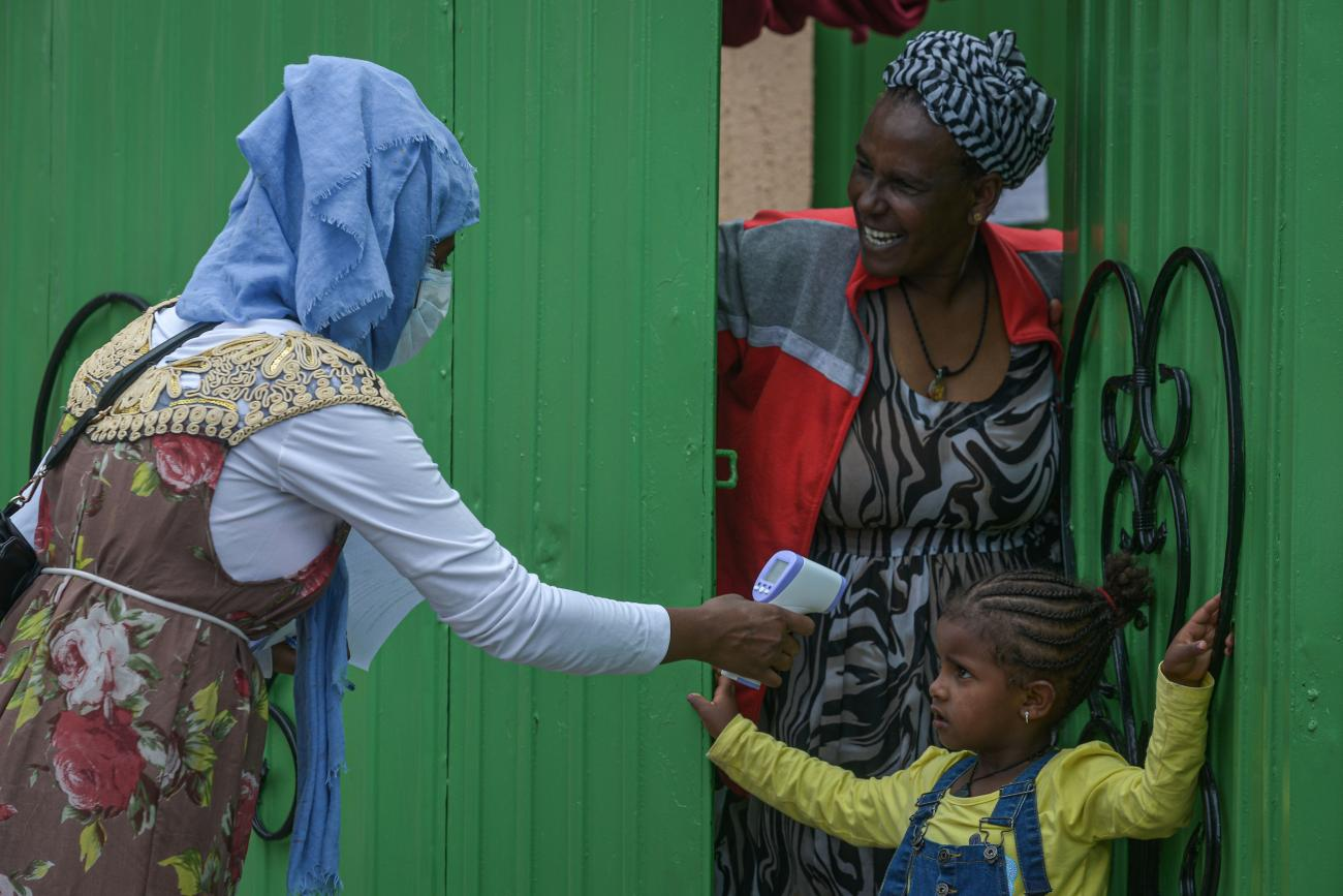 Woman health extension worker takes the temperature of a young girl outside a green door is Addis Ababa, Ethiopia.
