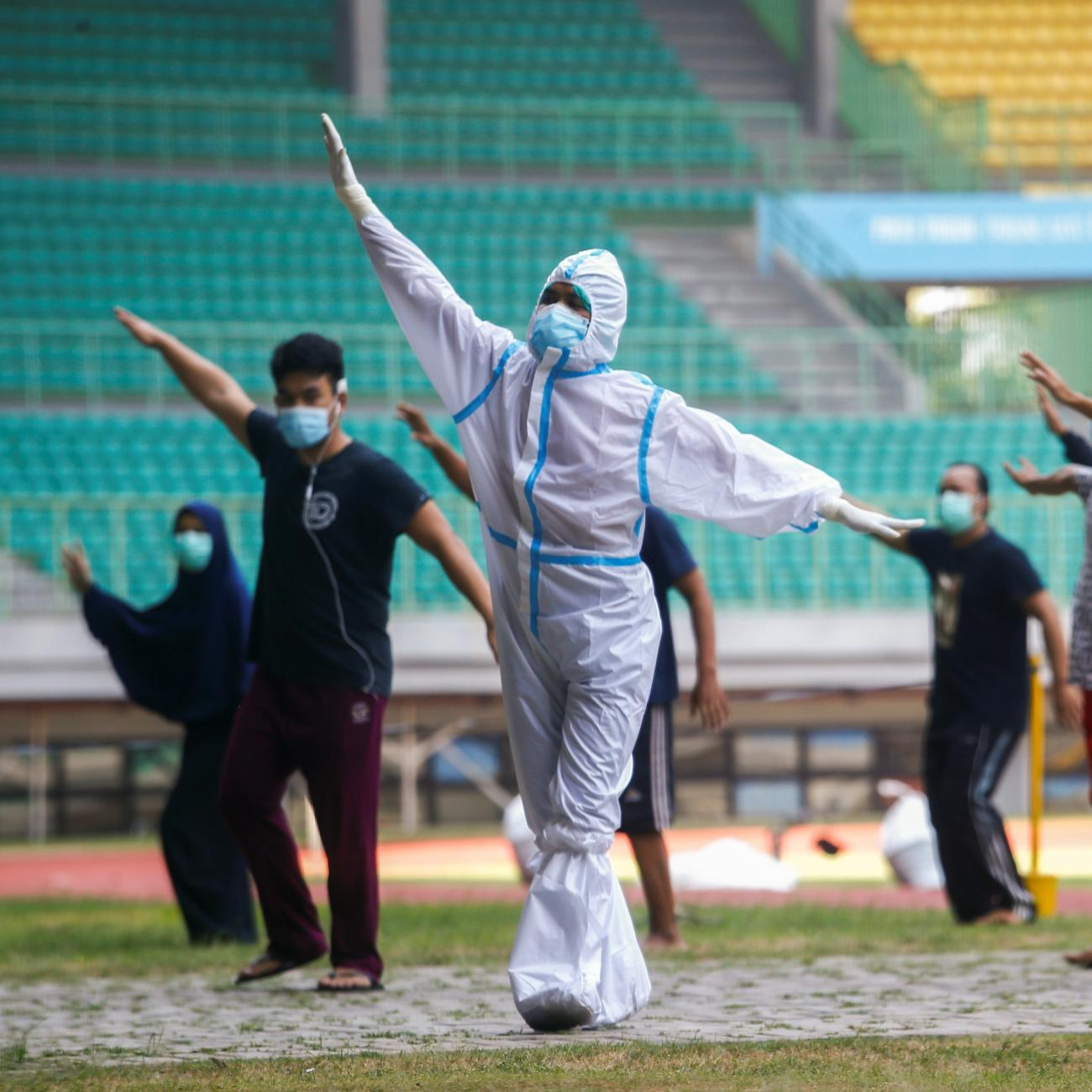 A health worker wearing protective suit and patients exercise at the Patriot Chandrabhaga Stadium which has been converted into a quarantine house amid the coronavirus disease (COVID-19) outbreak, in Bekasi, on the outskirts of Jakarta, Indonesia