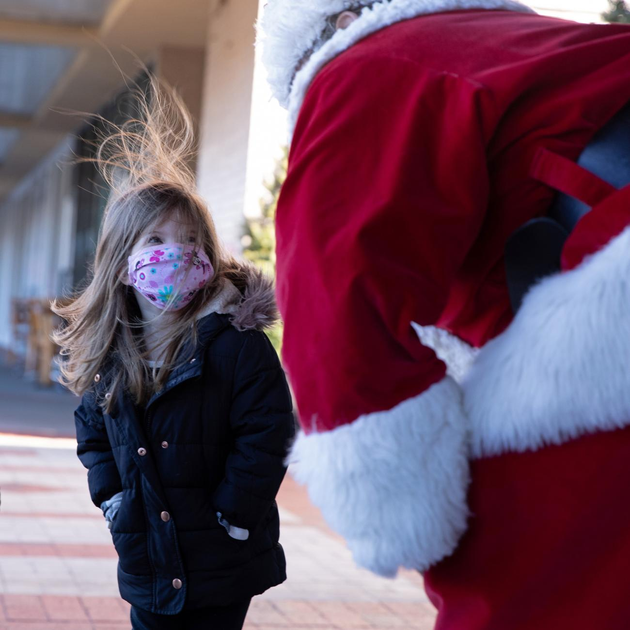 Santa Claus greets a young girl outside, both wearing masks as a precautionary measure in Queens as the global outbreak of the coronavirus disease continues in New York City on December 6, 2020.