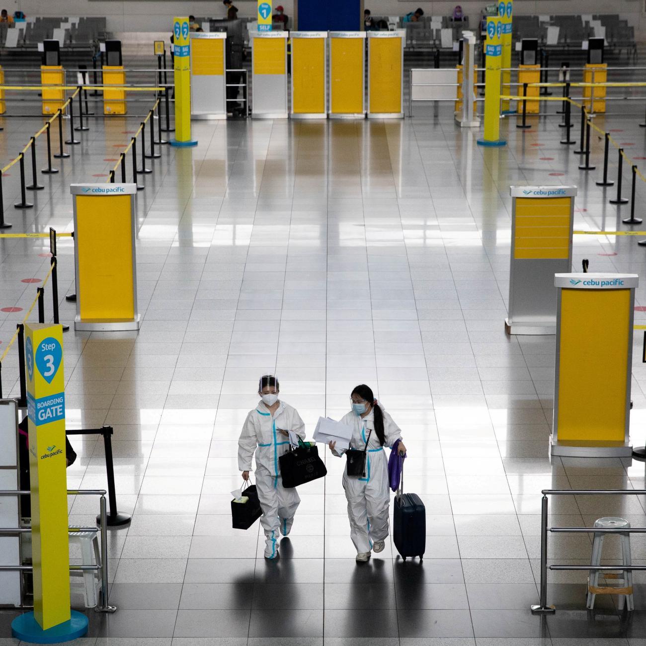 Passengers wearing hazmat suits for protection against the coronavirus disease walk inside the Ninoy Aquino International Airport in Paranaque, Metro Manila, Philippines on January 14, 2021.
