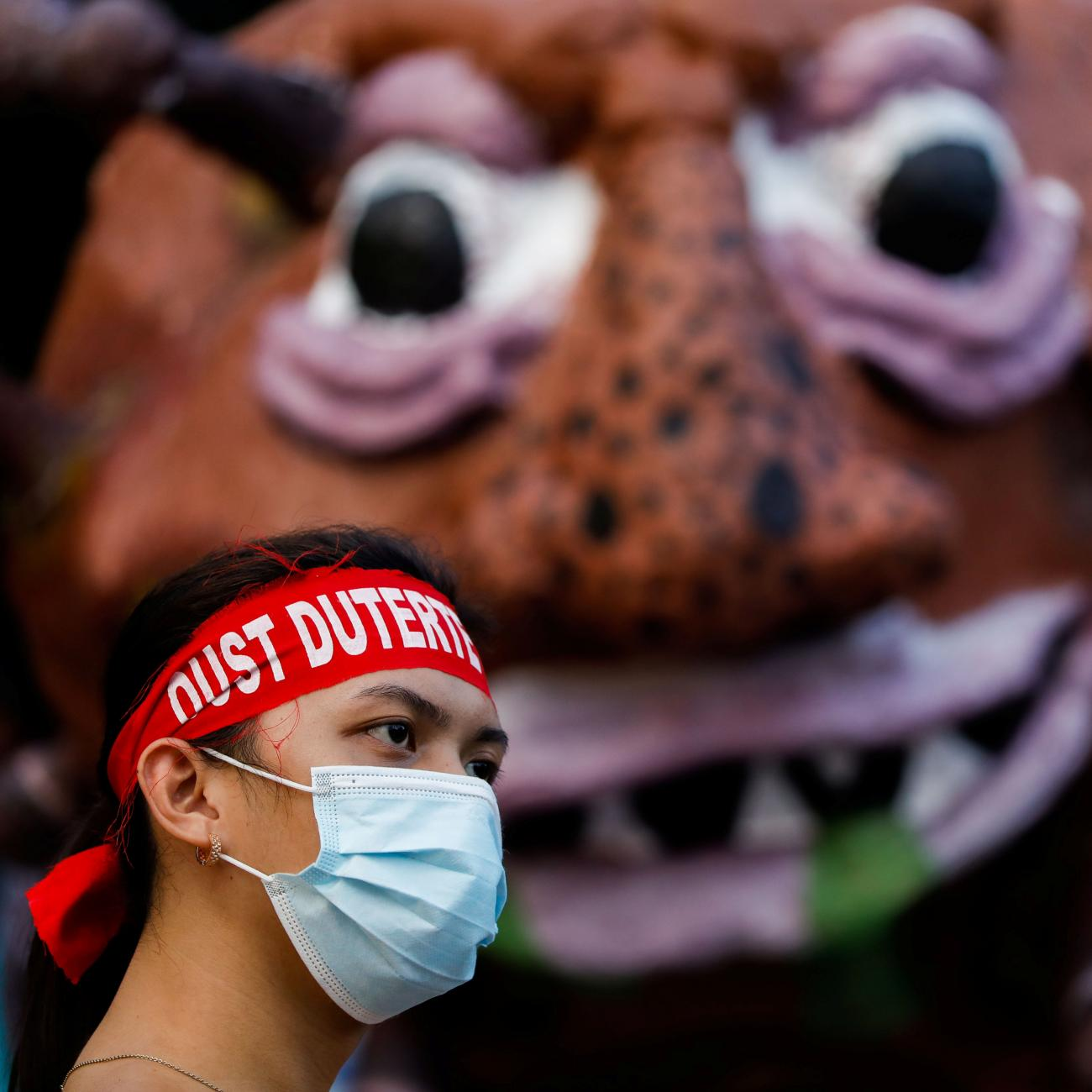 "An activist wearing a statement band that writes ""Oust Duterte"" is photographed in front of an effigy dubbed ""Duterte Virus"" during a protest in Manila, Philippines on September 21, 2020."