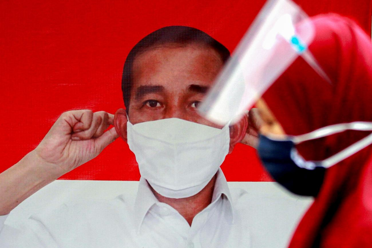 A woman walks past a banner depicting Indonesian President Joko Widodo promoting awareness of the coronavirus disease in Jakarta, Indonesia on September 28, 2020.