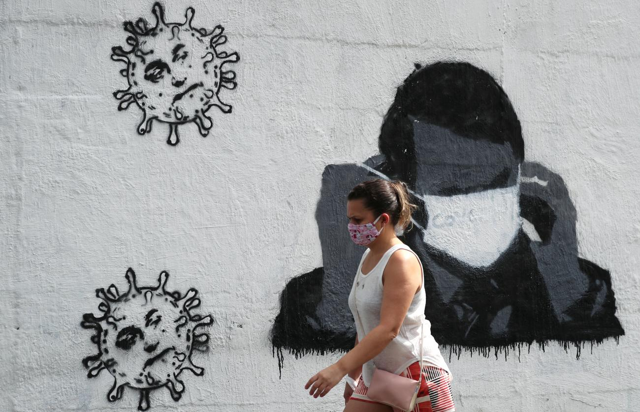 A woman walks past by a graffiti depicting Brazil's President Jair Bolsonaro adjusting his protective face mask and viruses, amid the coronavirus disease (COVID-19) outbreak in Rio de Janeiro, Brazil on July 2, 2020.