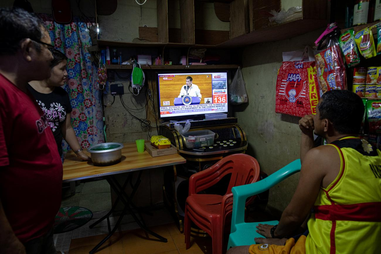 Filipinos watch President Rodrigo Duterte's fifth State of the Nation Address from a television attached on a karaoke inside a home, in Quezon City, Metro Manila, Philippines, July 27, 2020.