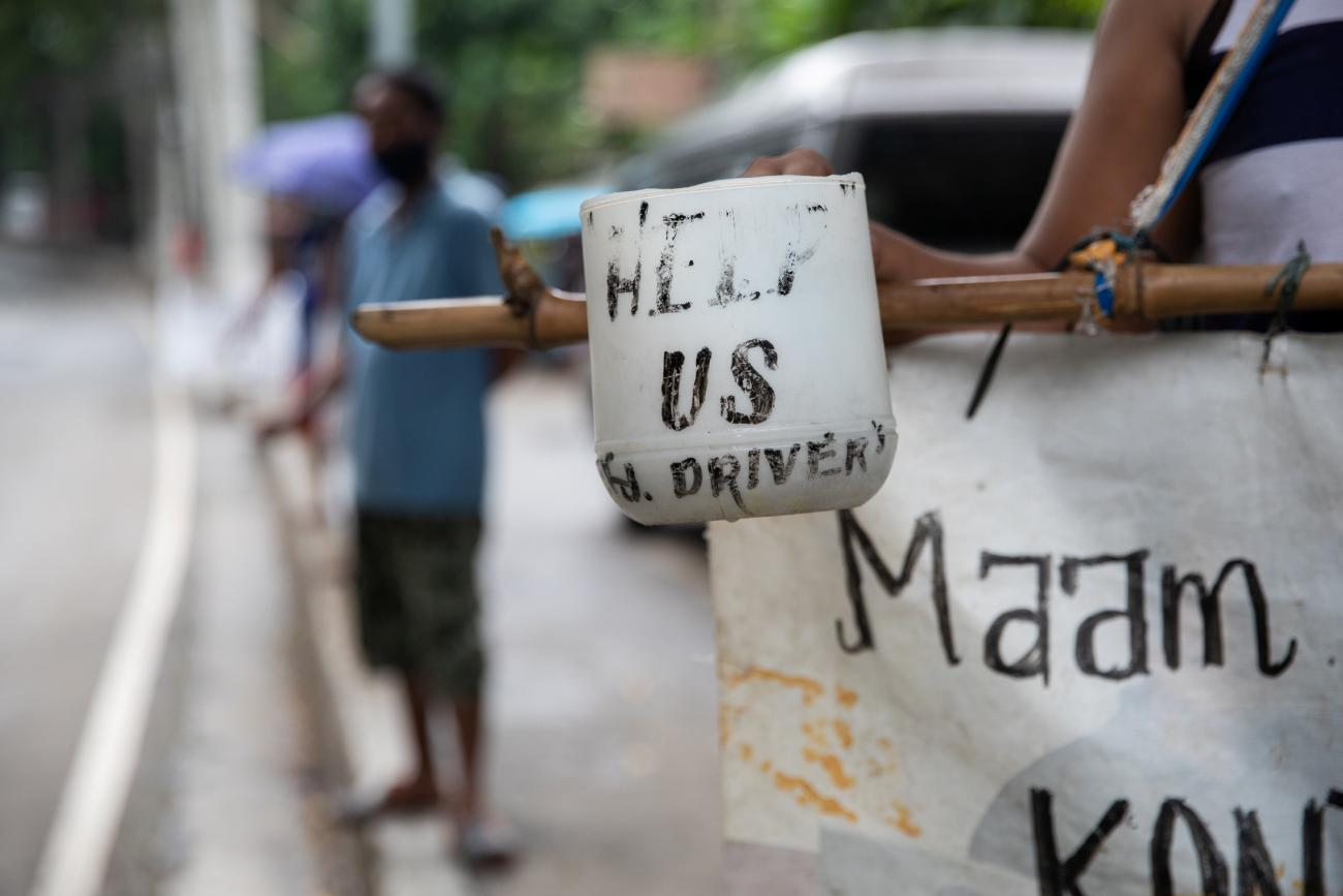 "A plastic cup with the words ""help us"" is held by a jeepney driver who lost his livelihood amid the coronavirus disease outbreak, on a roadside in Quezon City, Metro Manila, Philippines on July 30, 2020."