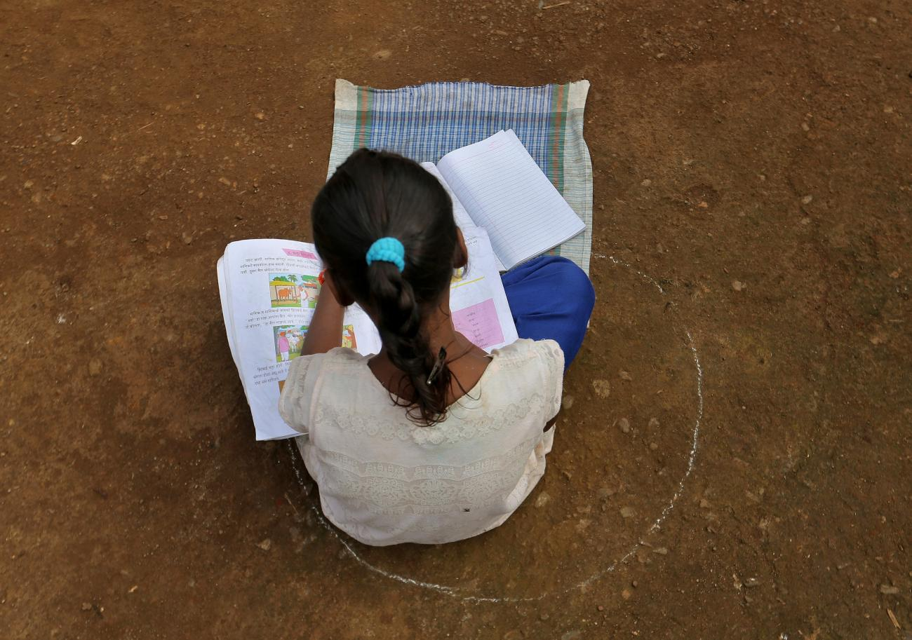 A girl, who has missed her online classes due to a lack of internet facilities, sits on the ground in a circle drawn with chalk to maintain safe distance as she listens to pre-recorded lessons over loudspeakers, after schools were closed following the coronavirus disease (COVID-19) outbreak, in Dandwal village in the western state of Maharashtra,