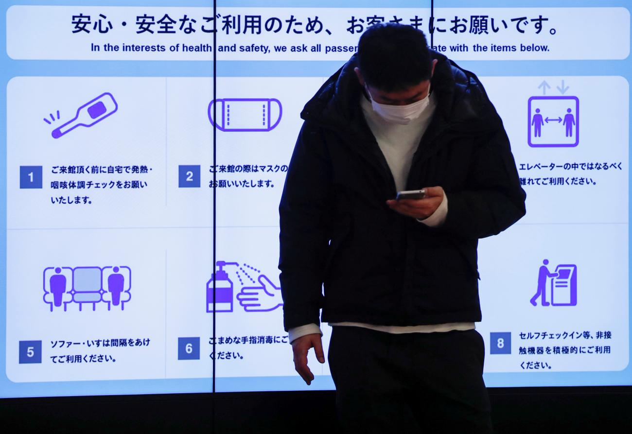 A man wearing a protective face mask stands in front of an electric screen displaying initiatives to prevent infections at Tokyo International Airport in Japan on Japan December 28, 2020.