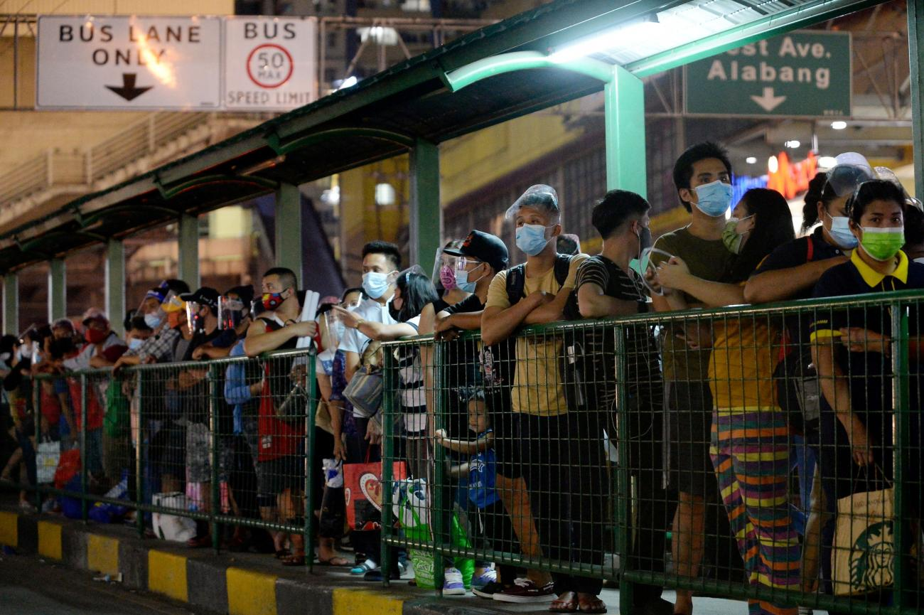 People wearing face masks and face shields as protection against the coronavirus disease queue at a bus stop, in Quezon City, Metro Manila, Philippines on December 23, 2020.
